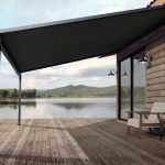 Wooden house exterior with beautiful lake and mountain view 3d render,There are old wood terrace floor,Decorate with white fabric chair,Surrounded by nature